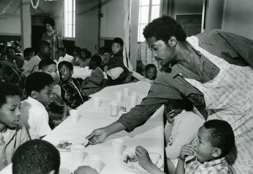 Charles Bursey hands a plate of food to a child seated at a Free Breakfast Program.