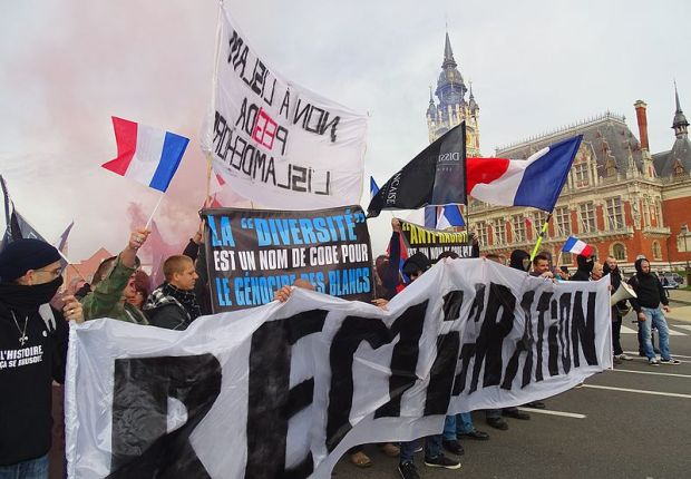 "French protesters in Calais hold banners saying ""Reimmigrate"" and ""Diversity is a code word for white genocide"", 8 November 2015"